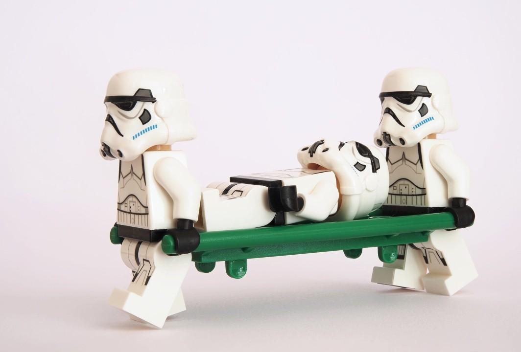 Zwei Lego-Stormtrooper tragen einen Lego-Stormtroober auf einer Trage.
